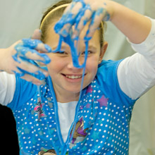 girl at Great Lakes Science Center with blue goo